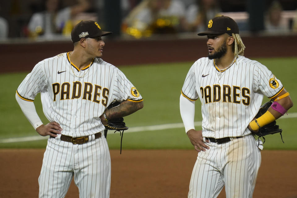 San Diego Padres third baseman Manny Machado, left, and shortstop Fernando Tatis Jr., right, talk in the infield during Game 3 of a baseball National League Division Series against the Los Angeles Dodgers Thursday, Oct. 8, 2020, in Arlington, Texas. (AP Photo/Sue Ogrocki)