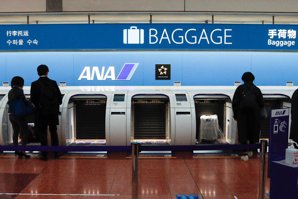 TOKYO, JAPAN - 2021/03/11: Passengers use automatic baggage check-in machines as All Nippon Airways (ANA) launches the baggage machine with newly developed touchless screen which has optical sensors on its frame of the screen at the Haneda airport in Tokyo.  All Nippon Airways Co. said it will suspend services on 16 international flight routes from late March due to falling travel demand amid the coronavirus pandemic. (Photo by James Matsumoto/SOPA Images/LightRocket via Getty Images)