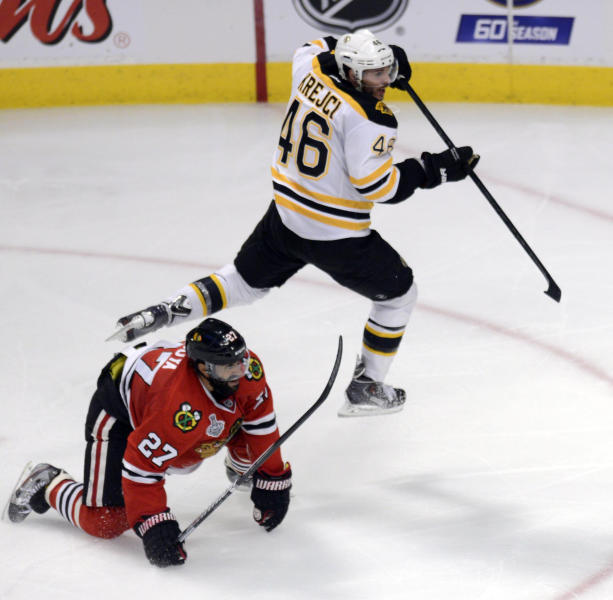 Boston Bruins center David Krejci jumps over Chicago Blackhawks defenseman Johnny Oduya in the third period during Game 1 in the NHL Stanley Cup Final hockey series , Wednesday, June 12, 2013, in Chicago. The Blackhawks won 4-3. (AP Photo/Daily Herald, John Starks)