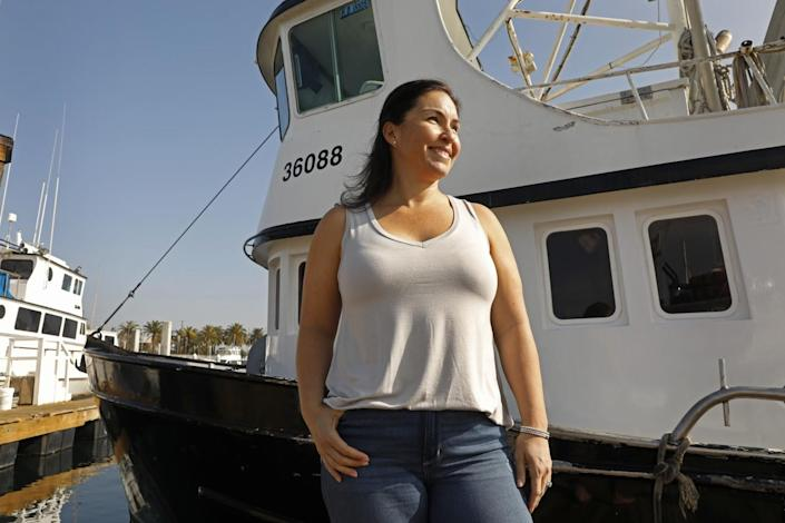 Desiree Rodriguez stands by a boat