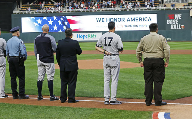Players from both teams, including New York Yankees manager Aaron Boone (17), joined with police and first responders during the national anthem following a tribute to 9/11 victims and survivors prior to a baseball game between the Minnesota Twins and the Yankees, Tuesday, Sept. 11, 2018, in Minneapolis. Tom Barnett Jr. was aboard Flight 93 which went down in Pennsylvania. (AP Photo/Jim Mone)
