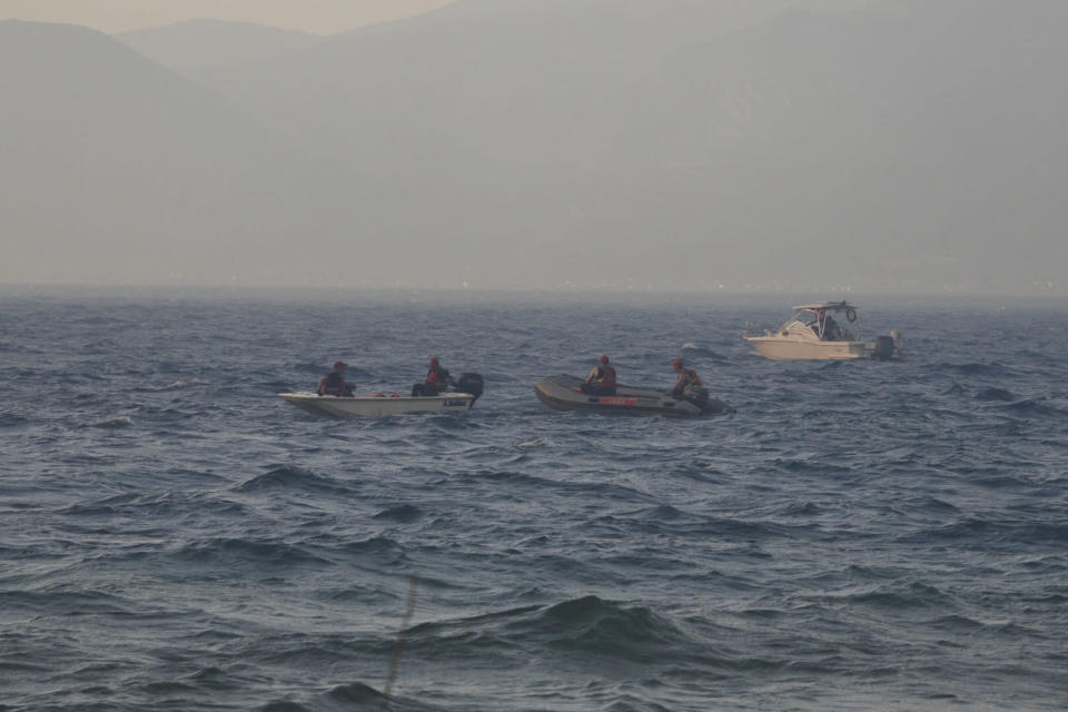 Firefighters and volunteers in vessels stand by the beach during a wildfire near Lampiri village, west of Patras, Greece, Saturday, Jul. 31, 2021. The fire, which started high up on a mountain slope, has moved dangerously close to seaside towns and the Fire Service has send a boat to help in a possible evacuation of people. (AP Photo/Andreas Alexopoulos)