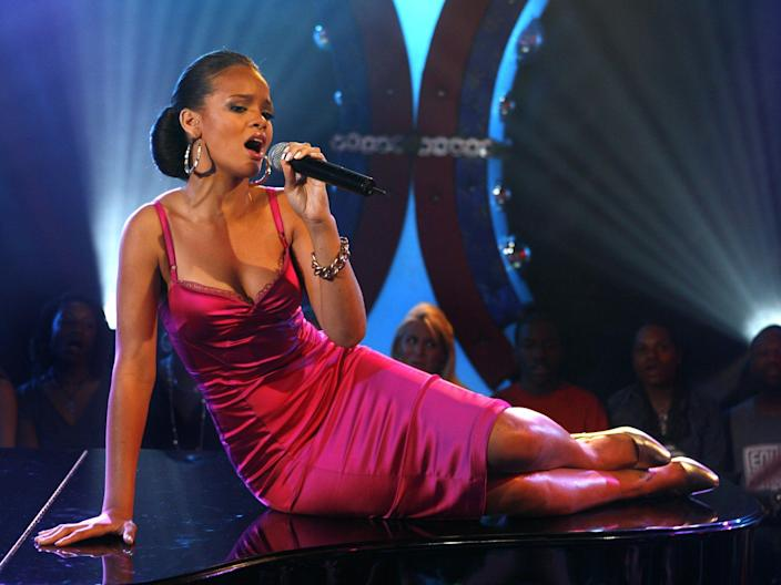 Rihanna sitting onstage singing wearing a pink dress in 2006