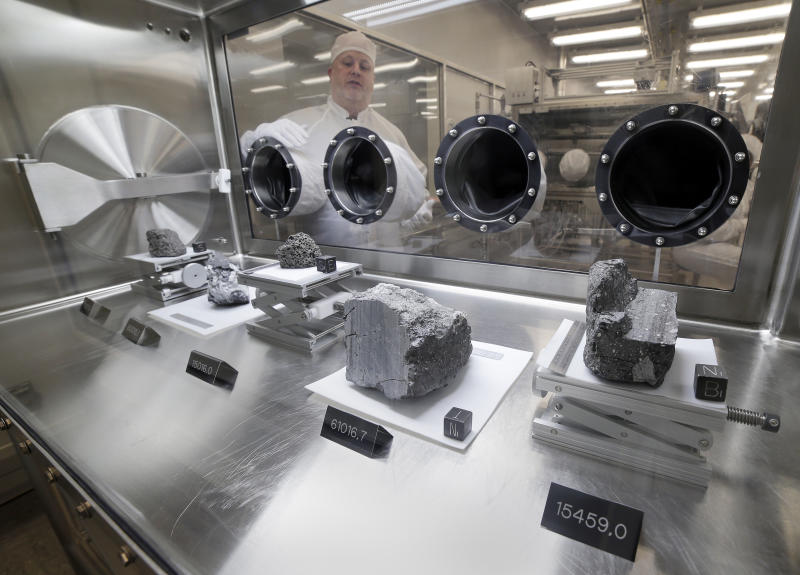 Ryan Zeigler, Apollo sample curator, left, stands next to a nitrogen-filled case displaying various lunar samples collected during Apollo missions 15, 16 and 17, inside the lunar lab at the NASA Johnson Space Center Monday, June 17, 2019, in Houston. (Photo: Michael Wyke/AP)