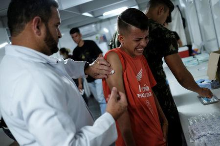 A Venezuelan boy receives a free vaccination given by a volunteer after showing his passport at the Pacaraima border control, Roraima state, Brazil August 9, 2018. REUTERS/Nacho Doce