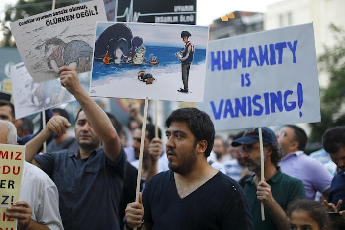 People hold posters with drawings depicting a drowned Syrian toddler during a demonstration for refugee rights in Istanbul, Turkey, September 3, 2015. The distraught father of two Syrian toddlers who drowned with their mother and several other migrants as they tried to reach Greece identified their bodies on Thursday and prepared to take them back to their home town of Kobani. Abdullah Kurdi collapsed in tears after emerging from a morgue in the city of Mugla near Bodrum, where the body of his three-year old son Aylan washed up on Wednesday. The image of Aylan, drowned off one of Turkey's most popular holiday resorts, went viral on social media and piled pressure on European leaders. Abdullah's family had been trying to emigrate to Canada after fleeing the war-torn town of Kobani, a revelation which also put Canada's Conservative government under fire from its political opponents. REUTERS/Osman Orsal