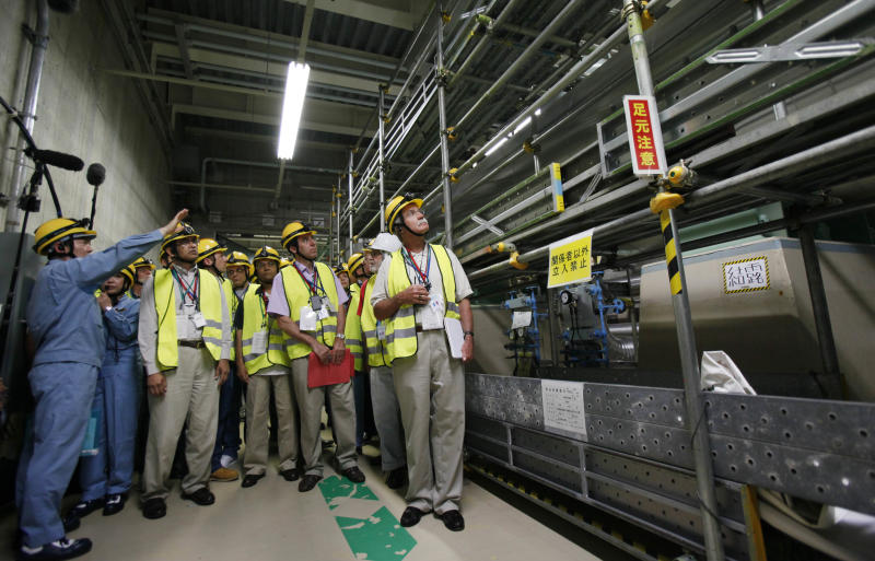 International Atomic Energy Agency group head Sujit Samaddar, second from left, and other experts inspect the heat exchanger at the Onagawa nuclear power plant in Onagawa, Miyagi prefecture, northeastern Japan, Tuesday, July 31, 2012. The 20-member IAEA mission, first at the Onagawa nuclear power plant, about 120 kilometers (74 miles) north of Fukushima Dai-ichi nuclear plant, since the crisis, aims to find out the extent of damage at the plant from the magnitude 9.0 quake. (AP Photo/Koji Sasahara)
