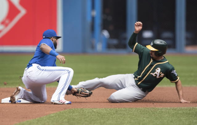 Oakland Athletics' Marcus Semien, right, is caught while trying stealing second by Toronto Blue Jays' Richard Urena, left, during first-inning baseball game action in Toronto, Sunday, May 20, 2018. (Fred Thornhill/The Canadian Press via AP)