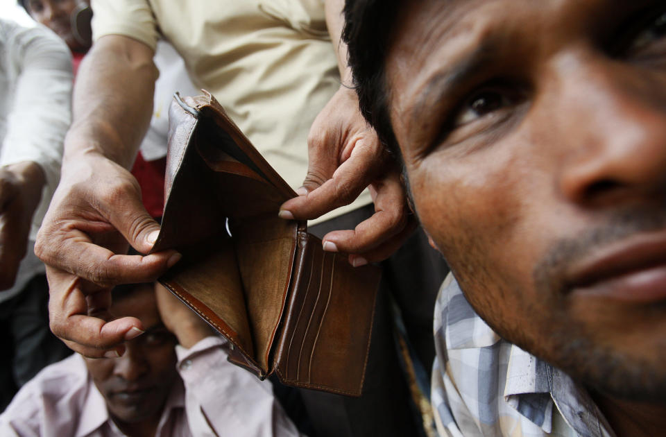 A migrant worker from Bangladesh shows his empty wallet to the camera as workers gather near a government office in Singapore on February 16, 2009. REUTERS/Vivek Prakash