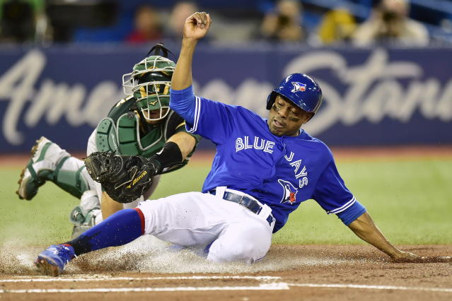 Toronto Blue Jays' Curtis Granderson, right, is tagged out at home plate by Oakland Athletics catcher Josh Phegley, left, during first-inning baseball game action in Toronto, Friday, May 18, 2018. (Frank Gunn/The Canadian Press via AP)