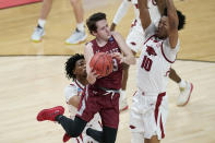 Colgate's Jack Ferguson (13) makes a pass against Arkansas' Jaylin Williams (10) during the first half of a first round game at Bankers Life Fieldhouse in the NCAA men's college basketball tournament, Friday, March 19, 2021, in Indianapolis. (AP Photo/Darron Cummings)