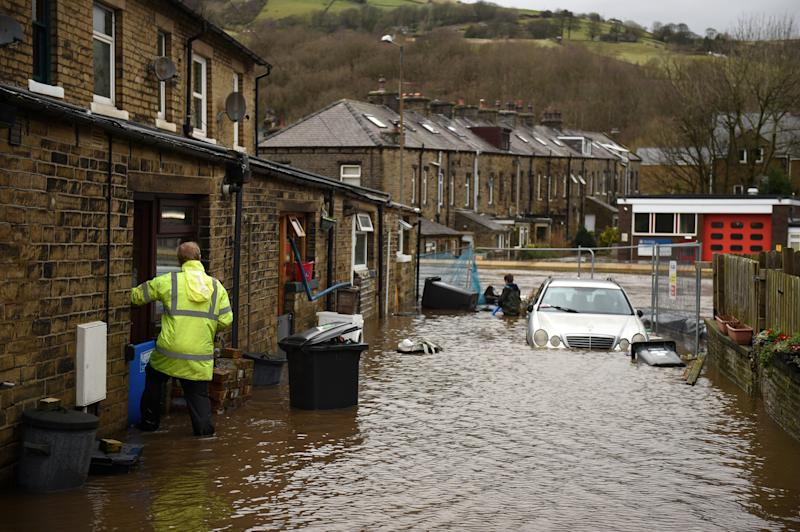 A man enters a house on a flooded street in Mytholmroyd, northern England, on February 9, 2020, after the River Calder burst its banks as Storm Ciara swept over the country. - Britain and Ireland hunkered down Sunday for a powerful storm expected to disrupt air, rail and sea links, cancel sports events, cut electrical power and damage property. With howling winds and driving rain, forecasters said Ciara would also hit France, Belgium, the Netherlands, Switzerland and Germany. (Photo by Oli SCARFF / AFP) (Photo by OLI SCARFF/AFP via Getty Images)