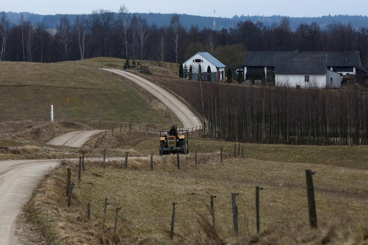 A man drives a tractor near Polish-Lithuanian border in Poszeszupie-Folwark village, Suwalki region, Poland March 25, 2017. Picture taken on March 25, 2017. REUTERS/Kacper Pempel