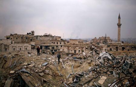 File photo: A member of forces loyal to Syria's President Bashar al-Assad stands with a civilian on the rubble of the Carlton Hotel, in the government controlled area of Aleppo