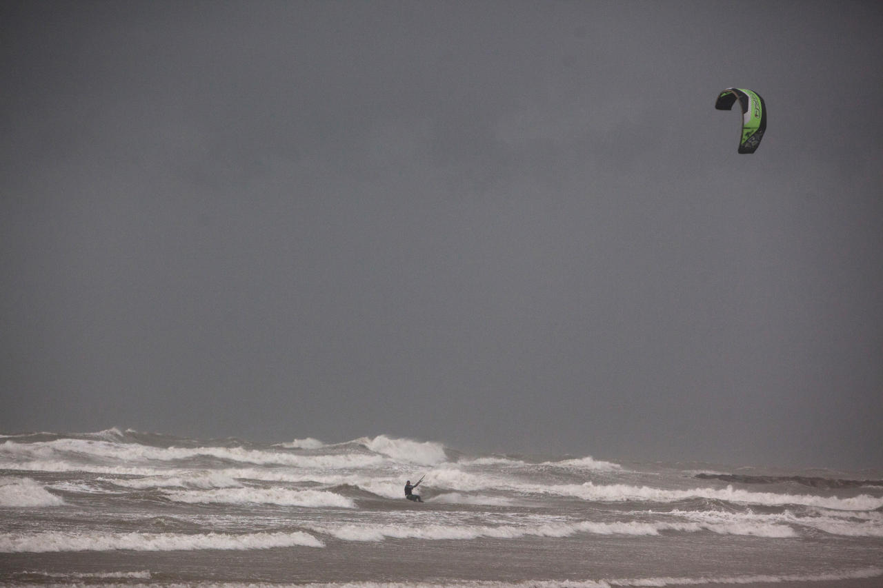 A man kitesurfs in the Mediterranean Sea in Tel Aviv during stormy weather January 8, 2013. Unusually heavy winter rains forced the closure of main access routes to Tel Aviv on Tuesday, causing gridlock in and around Israel's commercial capital, authorities said. REUTERS/Nir Elias (ISRAEL - Tags: ENVIRONMENT SOCIETY SPORT)