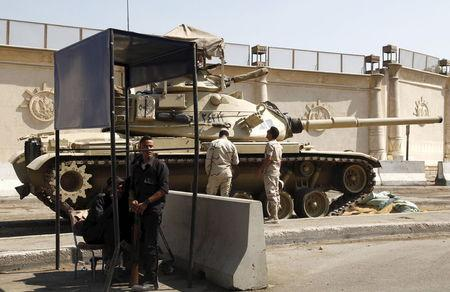 Police and army soldiers are seen in front of a tank as they guard outside Tora prison in Cairo