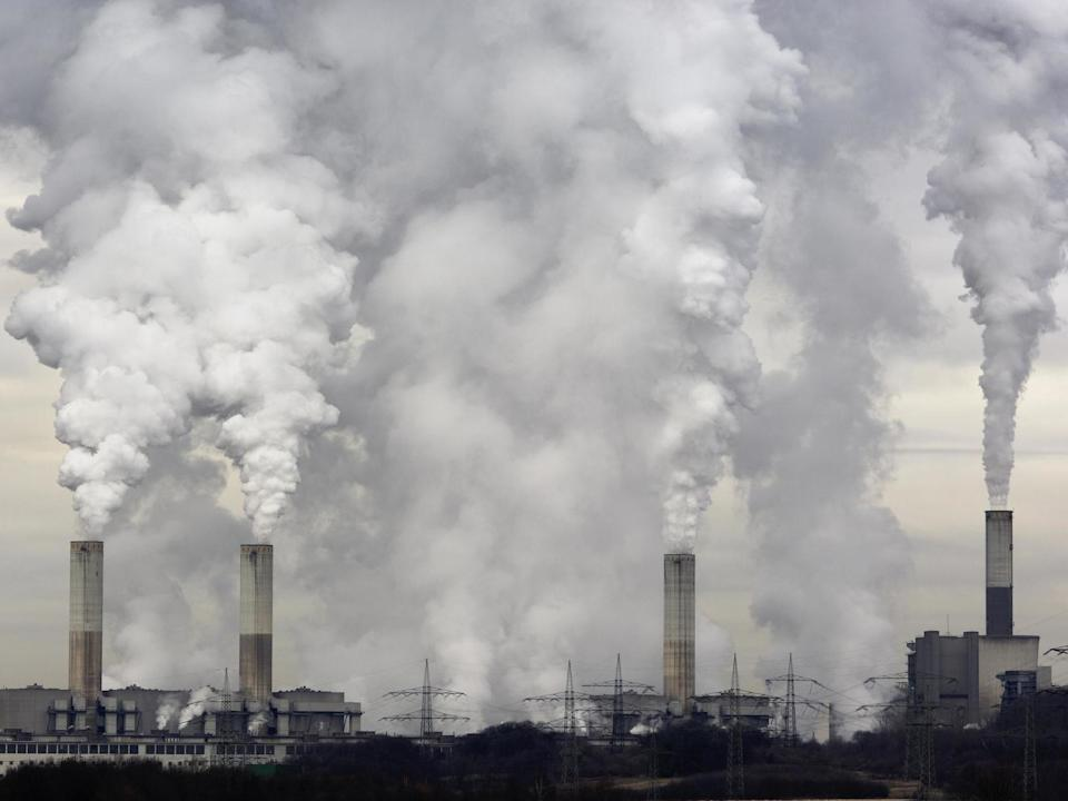 Smokestacks of a coal burning power plant with pollution on a cloudy day. (Getty)