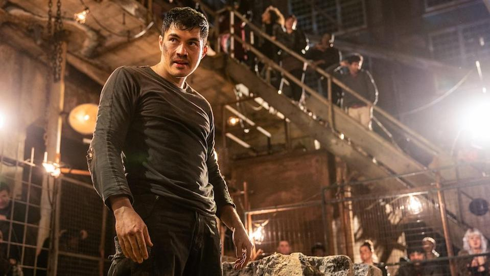 A bloodied Henry Goulding stands in a fighting pit as many people look on in Snake Eyes