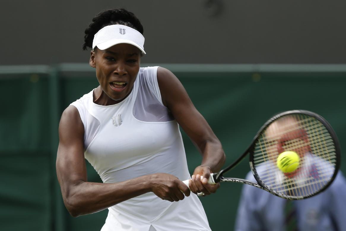 Venus Williams of the U.S. plays a return to Maria-Teresa Torro-Flor of Spain during their first round match at the All England Lawn Tennis Championships in Wimbledon, London, Monday, June 23, 2014. (AP Photo/Sang Tan)