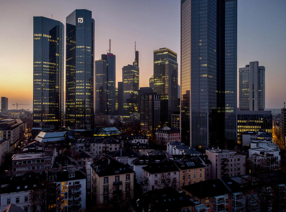 Lights glow in the windows of buildings of the banking district in Frankfurt, Germany, before sunrise on Wednesday, March 24, 2021. (AP Photo/Michael Probst)