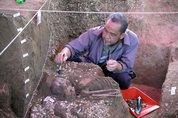 Archaeologist Prof Datuk Dr Mokhtar Saidin slowly uncovering the skeleton found at the Guar Kepah site.