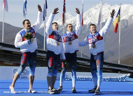 (L-R) Winners Russia's Alexey Voevoda, Dmitry Trunenkov,Alexey Negodaylo and pilot Alexander Zubkov, wave to spectators during a medal ceremony for the four-man bobsleigh event at the Sochi 2014 Winter Olympics, at the Sanki Sliding Center in Rosa Khutor February 23, 2014. REUTERS/Fabrizio Bensch