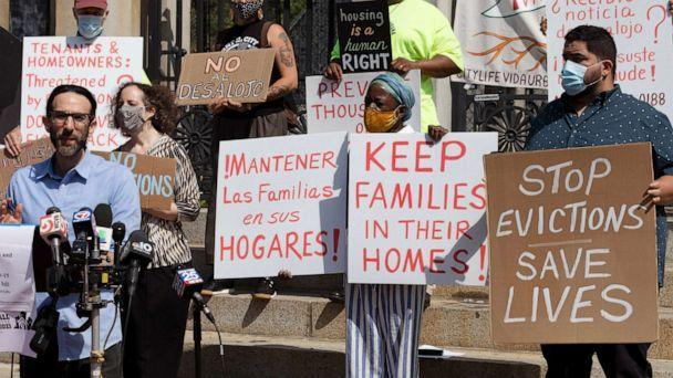PHOTO: People from a coalition of housing justice groups hold signs protesting evictions during a news conference outside the Statehouse, Friday, July 30, 2021, in Boston. (Michael Dwyer/AP)