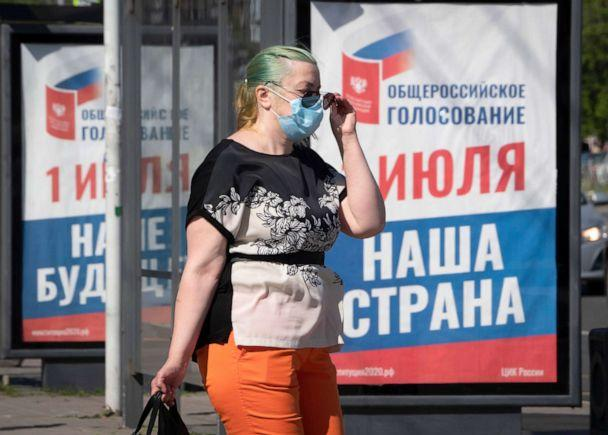 PHOTO: A woman, wearing a face mask to protect again coronavirus, walks past a billboard in St.Petersburg, Russia. (Dmitri Lovetsky/AP)