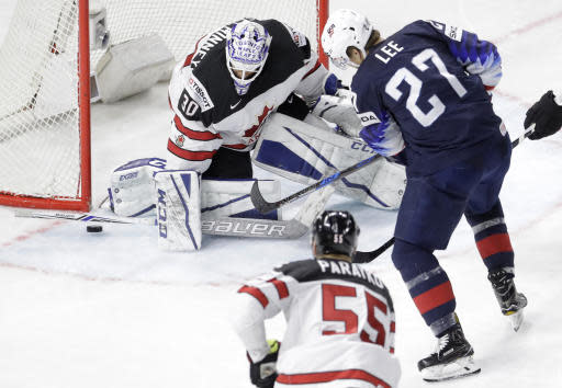 Canada's goalie Curtis McElhinney makes a save against Anders Lee of the United States during the Ice Hockey World Championships bronze medal match between Canada and the United States at the Royal arena in Copenhagen, Denmark, Sunday, May 20, 2018. (AP Photo/Petr David Josek)