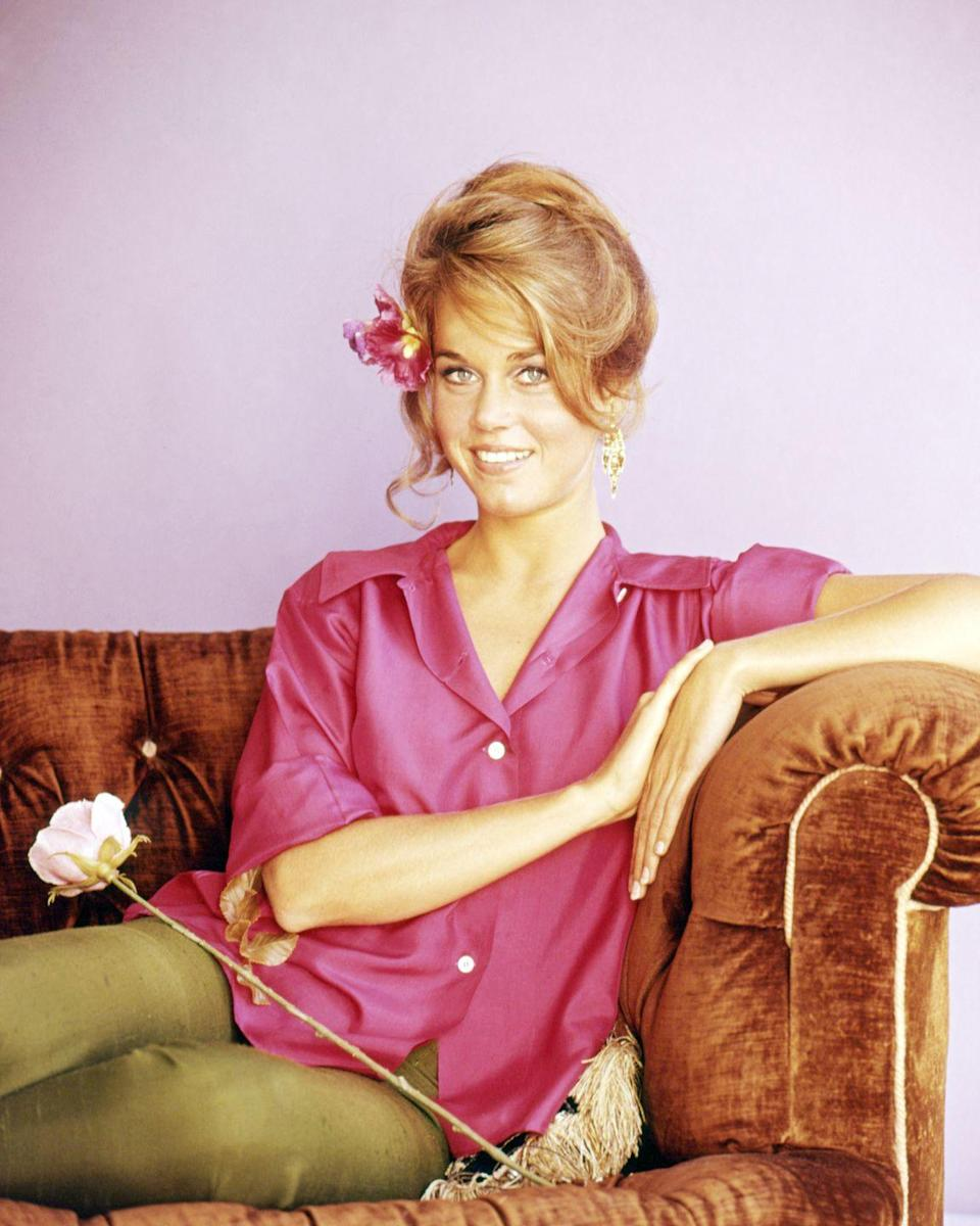 <p>A 30-year-old Jane Fonda poses in a bright pink shirt and green pants, with a flower in her hair. <br></p>