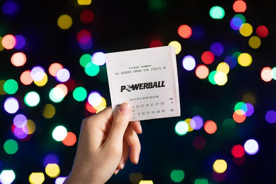 Lottery player holds up winning Powerball ticket. Source: The Lott