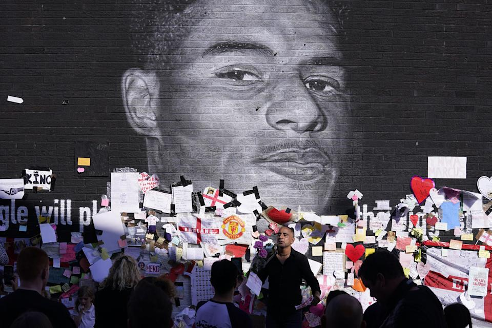 People gather to view the messages of support at a mural of England player Marcus Rashford in Manchester (Danny Lawson/PA) (PA Wire)