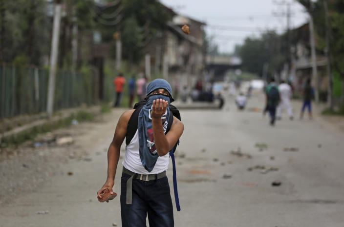 A Kashmiri prepares to catch a stone during an anti-India protest Srinagar, India, Friday, Aug. 9, 2019. The predominantly Muslim area has been under an unprecedented security lockdown and near-total communications blackout to prevent unrest and protests after India's Hindu nationalist-led government said Monday it was revoking Kashmir's special constitutional status and downgrading its statehood. (AP Photo/Altaf Qadri)