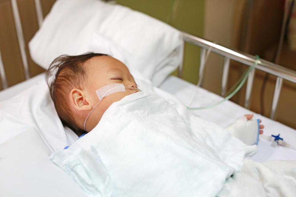 Baby boy with breathing tube in nose receiving medical treatment. Intensive care and attaching intravenous tube to hand on bed at hospital. Respiratory Syncytial Virus (RSV).