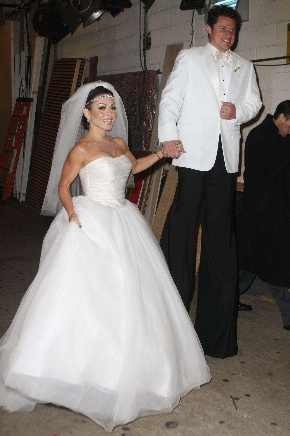 <p>TV host Kelly Ripa slayed in her Halloween costume as blushing bride Kim Kardashian with Nick Lachey as groom Kris Humphries towering above at the ABC TV studios in 2011.</p>
