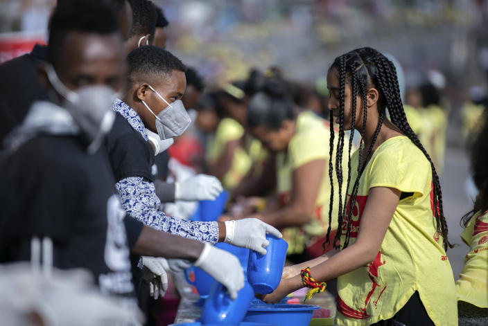 Volunteers, left, provide soap and water for participants to wash their hands against the new coronavirus at a women's 5km fun run in the capital Addis Ababa, Ethiopia Sunday, March 15, 2020. Ethiopia reported on Thursday its first case of the new coronavirus which causes COVID-19. For most people, the new coronavirus causes only mild or moderate symptoms, such as fever and cough but for some, especially older adults and people with existing health problems, it can cause more severe illness, including pneumonia. (AP Photo/Mulugeta Ayene)