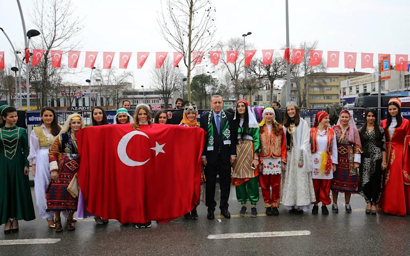 Erdogan, centre, poses for a photos with the members of a folklore group as he arrives to address his supporters in Sakarya, Turkey on Thursday - Credit: AP