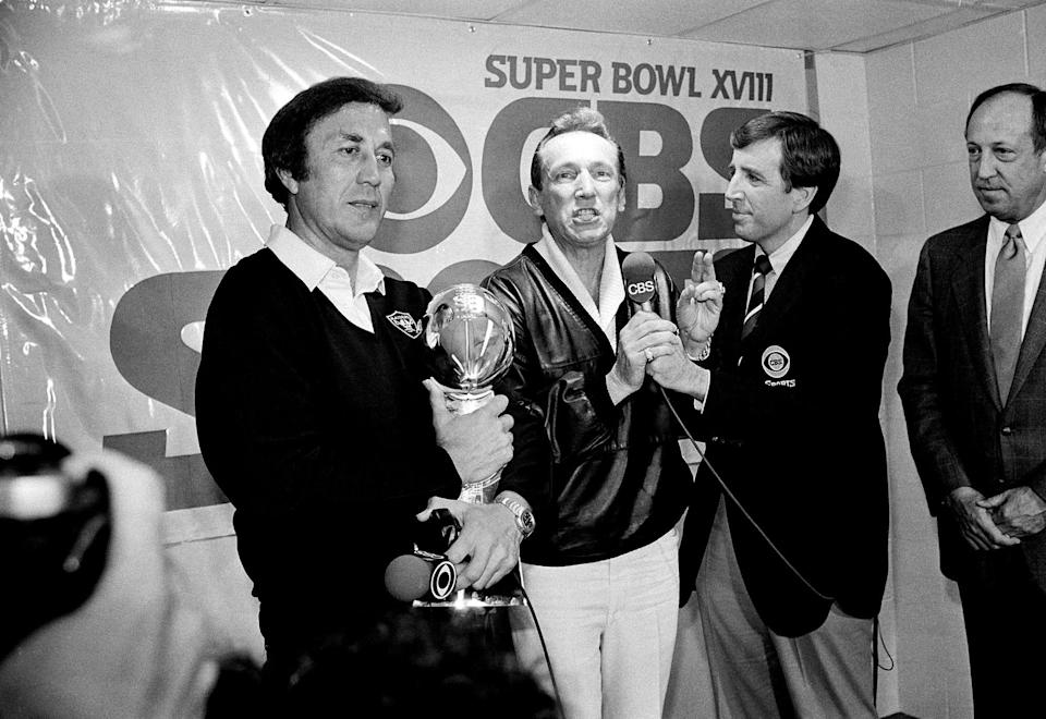 Raiders coach Tom Flores clutches the Super Bowl trophy as Raiders managing general partner Al Davis is interviewed by Brent Musburger in the locker room after their 38-9 win over the Washington Redskins in Super Bowl XVIII.
