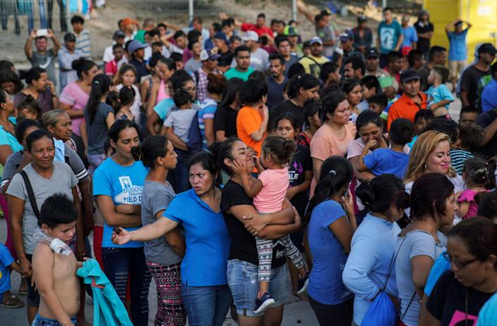 "In this Aug. 30, 2019, file photo, migrants, many who were returned to Mexico under the Trump administration's ""Remain in Mexico,"" program wait in line to get a meal in an encampment near the Gateway International Bridge in Matamoros."