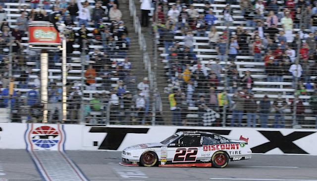 Brad Keselowski (22) takes the checkered flag as he wins the NASCAR Nationwide Series auto race at Texas Motor Speedway in Fort Worth, Texas, Saturday, Nov. 2, 2013. (AP Photo/Larry Papke)