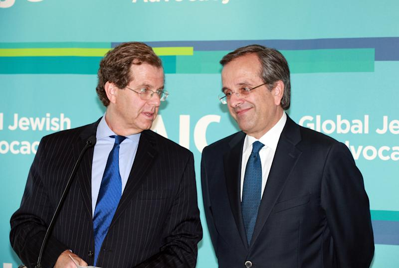 Greek Prime Minister Antonis Samaras, right, is welcomed by David Harris, left, American Jewish Committee (AJC) executive director as he addresses a breakfast meeting with leadership of the AJC in New York Monday, Sept. 30, 2013.(AP Photo/David Karp)