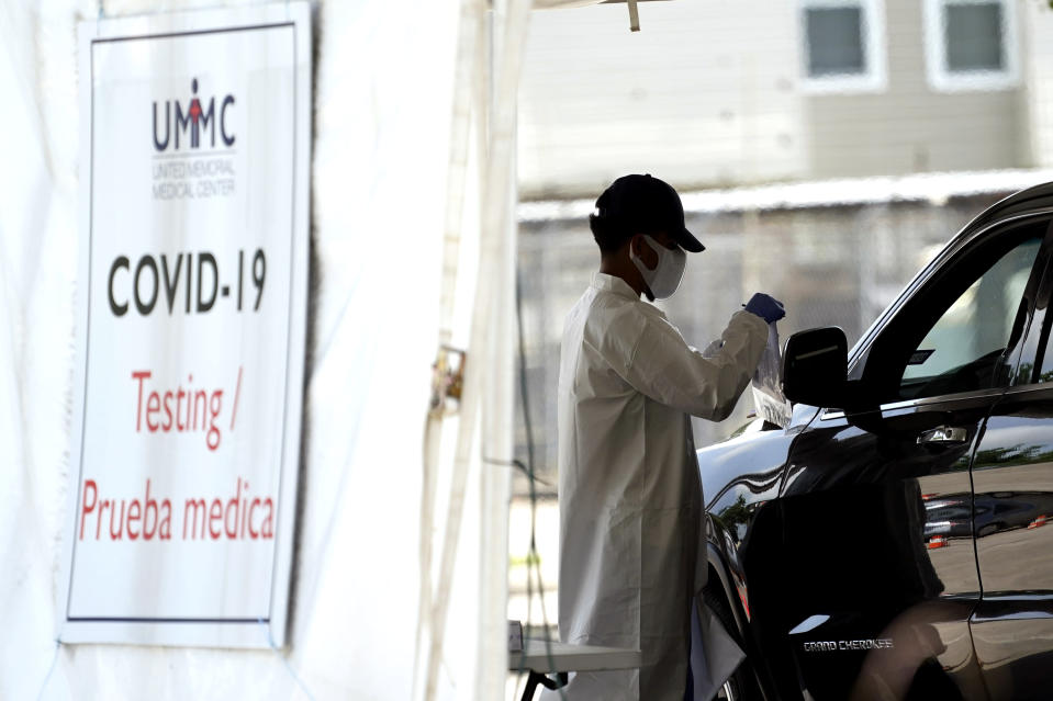 A healthcare worker gathers information from a patient at a United Memorial Medical Center COVID-19 testing site Thursday, July 16, 2020, in Houston. (AP Photo/David J. Phillip)