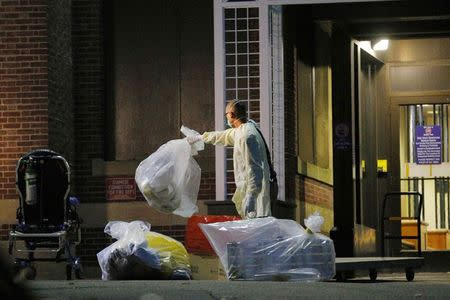 A man collects and bags items near the ambulance used to transport a patient with possible Ebola symptoms to Beth Israel Deaconess Medical Center in Boston, Massachusetts October 12, 2014. REUTERS/Brian Snyder