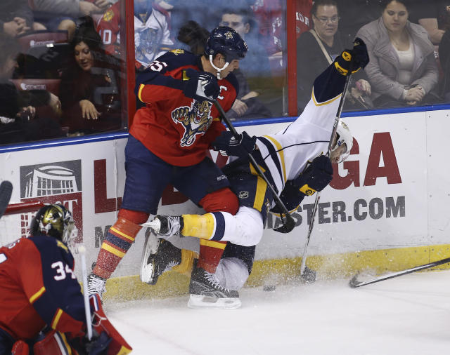 Florida Panthers' Ed Jovanovski (55) and Nashville Predators' Paul Gaustad (28) battle for the puck during the second period of a NHL hockey game in Sunrise, Fla., Saturday, Jan. 4, 2014. (AP Photo/J Pat Carter)
