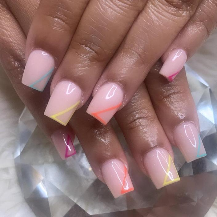 """You may be used to seeing dramatically long acrylic nails, but they don't always have to be lengthy. Just look at this manicure from Brooklyn-based nail artist <a href=""""https://www.instagram.com/talontedgrip/"""" rel=""""nofollow noopener"""" target=""""_blank"""" data-ylk=""""slk:Meisty Gawdess"""" class=""""link rapid-noclick-resp"""">Meisty Gawdess</a>. The length is perfect for those who are intimidated by longer styles or live a lifestyle where shorter nails are a must. We love each bright shade she chose to create the angled lines at the tips of this nude, square-shaped set."""