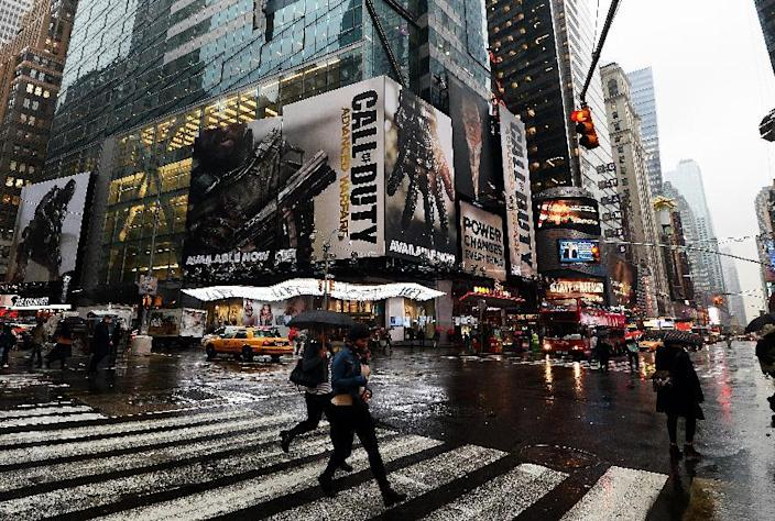 "People walk past billboards advertising ""Call of Duty: Advanced Warfare"" near Times Square in New York, November 6, 2014 (AFP Photo/Jewel Samad)"