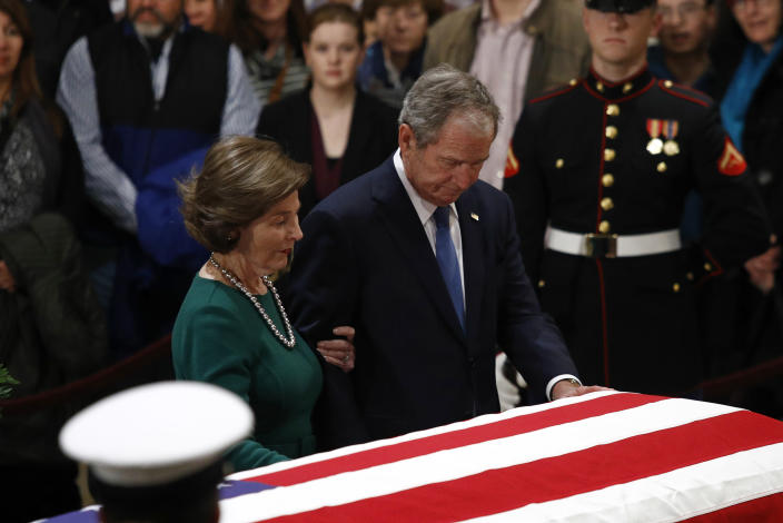 Former President George W. Bush and former first lady Laura Bush pause in front of the flag-draped casket of former President George H.W. Bush as he lies in state in the Capitol's Rotunda in Washington, Tuesday, Dec. 4, 2018. (Photo: Patrick Semansky/AP)