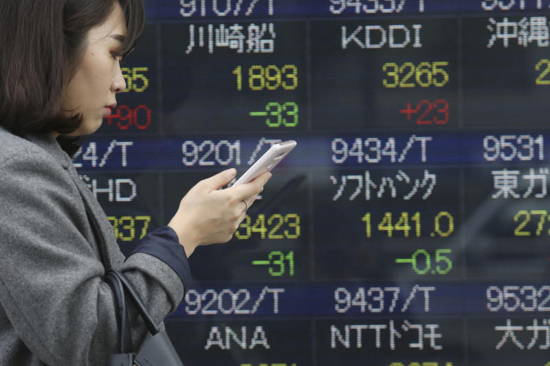 In this Wednesday, Dec. 18, 2019, photo, a woman walks by an electronic stock board of a securities firm in Tokyo.  Stocks were mixed in early trading in Asia on Friday after Wall Street posted more record highs, extending the market's gains for the week. (AP Photo/Koji Sasahara)