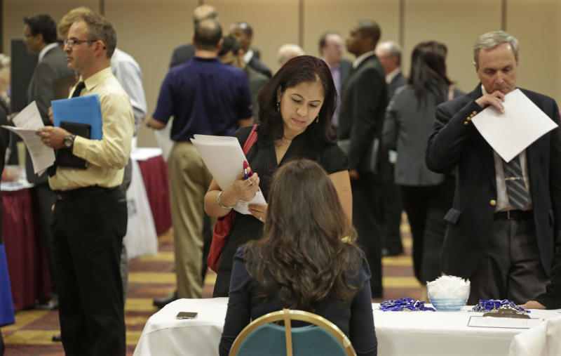 In this May 29, 2013 photo, job seeker Anu Vatal of Chicago, speaks with Patrice Tosi of BluePay, seated, during a career fair in Rolling Meadows, Ill. The Labor Department reports on the number of Americans who applied for unemployment benefits in the last week of May, on Thursday, May 30, 2013. (AP Photo/M. Spencer Green)