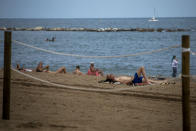 Tourists sunbathe in a beach in Barcelona, Spain, Thursday, July 16, 2020. With Europe's summer vacation season kicking into high gear for millions weary of months of lockdown, scenes of drunken British and German tourists on Spain's Mallorca island ignoring social distancing rules and reports of American visitors flouting quarantine measures in Ireland are raising fears of a resurgence of infections in countries that have battled for months to flatten the COVID-19 curve. (AP Photo/Emilio Morenatti)